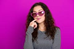 Il bello ritratto della giovane donna, posante sul fondo porpora, capelli ricci lunghi, occhiali da sole nel cuore modella, conce Fotografia Stock