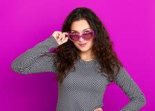 Il bello ritratto della giovane donna, posante sul fondo porpora, capelli ricci lunghi, occhiali da sole nel cuore modella, conce Fotografie Stock