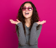 Il bello ritratto della giovane donna, posante sul fondo rosa, capelli ricci lunghi, occhiali da sole nel cuore modella, concetto Fotografia Stock Libera da Diritti