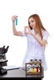 Il bello scienziato della donna in laboratorio realizza le varie operazioni Fotografie Stock