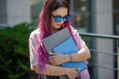 Il bello scrittore femminile del ritratto si è vestito in attrezzatura casuale che giudica il computer portatile moderno disponib Fotografia Stock Libera da Diritti