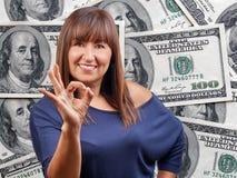 Il bello segno di approvazione della donna cento dollari di fatture ammucchia il fondo immagine stock libera da diritti