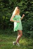 Il bello soggiorno biondo in foresta, corregge il vestito Immagine Stock Libera da Diritti