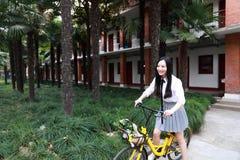 Il bello studente di college adorabile sveglio felice della High School della ragazza gode del giro di tempo libero una bici alla Fotografia Stock Libera da Diritti