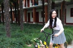 Il bello studente di college adorabile sveglio felice della High School della ragazza gode del giro di tempo libero una bici alla Fotografia Stock