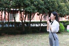 Il bello studente di college adorabile sveglio felice della High School della ragazza gode del tempo libero mangia il gelato Immagine Stock