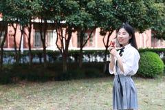 Il bello studente di college adorabile sveglio felice della High School della ragazza gode del tempo libero mangia il gelato Fotografia Stock Libera da Diritti