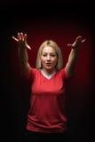 Il bello tifoso biondo della donna che salmodia con entrambe le armi si è alzato in maglietta rossa Fotografia Stock