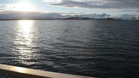 Il bello tramonto sopra catena montuosa nevosa vigorosa nel Circolo polare artico con cielo blu e calma ondeggia sull'acqua del f stock footage