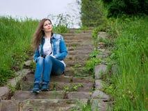 Il bello turista della ragazza in un rivestimento del cotone si siede sui punti di pietra d'annata e foto di presa con una macchi Immagine Stock