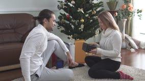 Il bello uomo dà il regalo di Natale alla sua moglie che si siede sul pavimento La ragazza graziosa è sorpresa piacevolmente e fe video d archivio