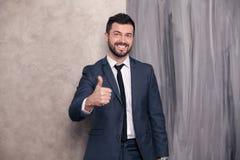 Il bello uomo d'affari felice bello sta stando nel suo ufficio che mostra il sospiro e sorridere freschi vestito d'uso e un legam immagine stock libera da diritti