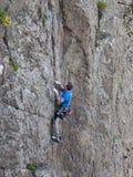 Il bello uomo scala un'alta montagna Fotografia Stock