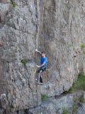 Il bello uomo scala un'alta montagna Immagine Stock