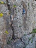 Il bello uomo scala un'alta montagna Fotografie Stock