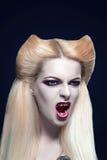 Il bello vampiro biondo della ragazza con sangue è sulla bocca e osserva Fotografia Stock