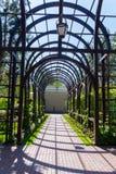 Il bello vicolo ha allineato con le mattonelle che passano attraverso un arco delle costruzioni metalliche Immagini Stock