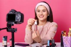 Il bello vlogger sorridente che mostra il suo nuovo rossetto agli abbonati, sembra felice, tenendolo in entrambe le mani, posare  fotografia stock libera da diritti