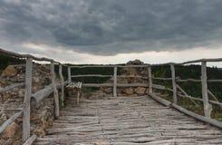 Il benche di legno sulle rovine del castello, negli ambiti di provenienza è cielo nuvoloso fotografie stock