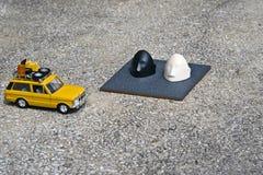 Il bianco, automobile pratica affrontata nera ha parcheggiato accanto ad una tomba Fotografia Stock Libera da Diritti