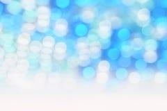 Il bianco circolare brillante del bokeh su fondo blu e svuota lo spazio per testo immagini stock libere da diritti