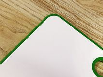 Il bianco con il tagliere verde si trova su una tavola di legno Utilizzato nella cucina Primo piano Immagine Stock