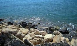 Il bianco e Mar Nero oscilla sulla spiaggia e sull'acqua brillante di scintillio Immagini Stock