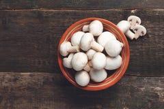 Il bianco fresco si espande rapidamente fungo prataiolo in ciotola marrone su fondo di legno Vista superiore Copi lo spazio immagine stock libera da diritti