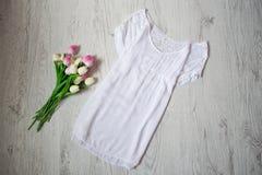 Il bianco ha allungato la blusa con pizzo, tulipani rosa Concetto alla moda, vista superiore Fotografia Stock