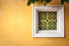 Il bianco ha incorniciato la finestra sulla parete dello stucco giallo. Fotografie Stock Libere da Diritti