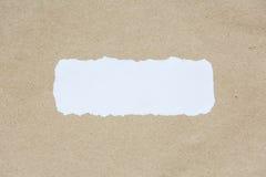 Il bianco ha strappato pezzo di carta sulla carta marrone di struttura del documento Fotografia Stock Libera da Diritti