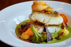 Il bianco ha stufato il pesce del pikeperch in salsa verde di pesto con le verdure per la cottura a vapore dei broccoli, carote,  Fotografie Stock