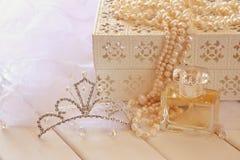 Il bianco imperla la collana, il diadema del diamante e la bottiglia di profumo Fotografie Stock