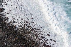 Il bianco ondeggia sul ciottolo vulcanico nero Immagine Stock Libera da Diritti