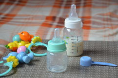 Il biberon con latte ed il cucchiaio per nei precedenti della formica del bambino gioca Immagine Stock