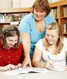 Il bibliotecario aiuta gli allievi Immagine Stock