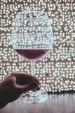 Il bicchiere di vino emette luce in lampade di migliaia fotografia stock