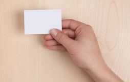 Il biglietto da visita in bianco ha tenuto su legno immagine stock