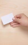 Il biglietto da visita in bianco ha tenuto su legno Fotografie Stock