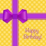 Il biglietto di auguri per il compleanno con i nastri viola e l'arco su giallo hanno punteggiato il backg Immagini Stock