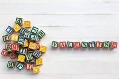 Il BIGLIETTO DI S. VALENTINO scrive in blocchetto di legno dell'alfabeto sul bordo di legno bianco fotografia stock libera da diritti