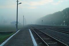 Il binario della stazione ferroviaria nella nebbia Fotografia Stock