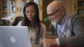 Il biologo Professor e la studentessa stanno parlando alla tavola con il computer portatile in biblioteca stock footage