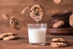 Il biscotto cade nel bicchiere di latte Fotografia Stock