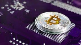 Il bitcoin della moneta d'argento gira contro il microchip video d archivio