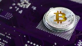 Il bitcoin della moneta d'argento gira contro il microchip stock footage