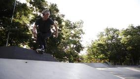 Il blader in-linea del rullo dell'uomo che esegue i salti al parco locale del pattino, giovane intestino sui pattini di rullo ese video d archivio