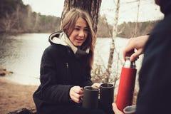 Il bloccaggio di stile di vita delle coppie che bevono il tè caldo all'aperto su accogliente riscalda la passeggiata in foresta immagine stock libera da diritti