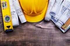 Il blocco note blueprints il metro di legno del casco e Fotografia Stock