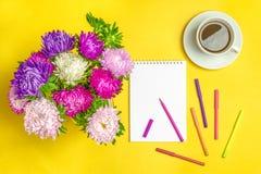 Il blocco note, fiori dell'aster, ha colorato i pennarelli, tazza con caffè su fondo giallo Autunno di concetto, estate, molla Immagine Stock